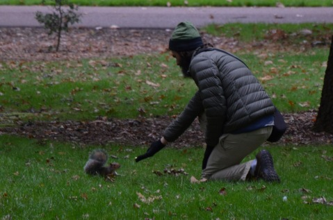 Homeless man feeds the squirrel