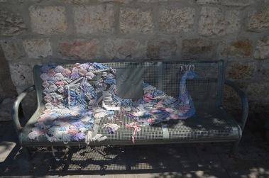 Crochet peacock on a park bench